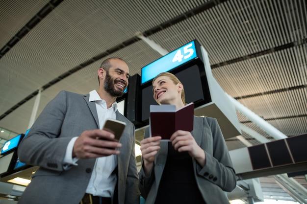 Ludzie biznesu posiadający kartę pokładową i korzystający z telefonu komórkowego