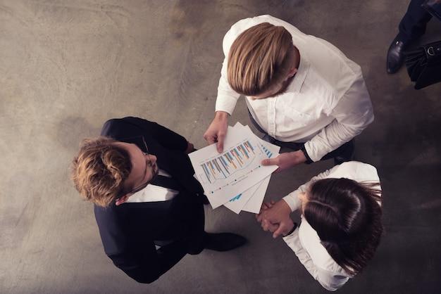 Ludzie biznesu pracują z numerami statystycznymi firmy
