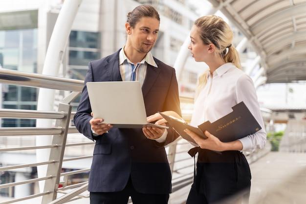 Ludzie biznesu pracujący i omawiający dane online przed laptopem