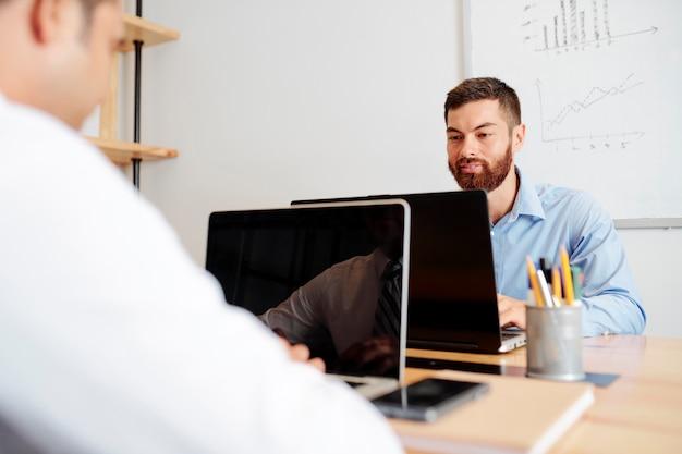 Ludzie biznesu pracujący na komputerach przenośnych