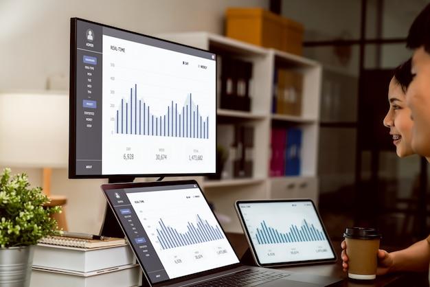 Ludzie biznesu pracujący na laptopach i wyświetlający wykresy statystyk na ekranach komputerów.