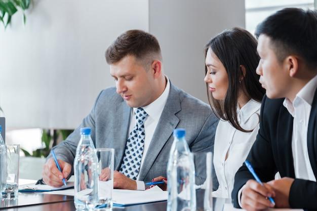 Ludzie biznesu pracuje razem przy stole konferencyjnym