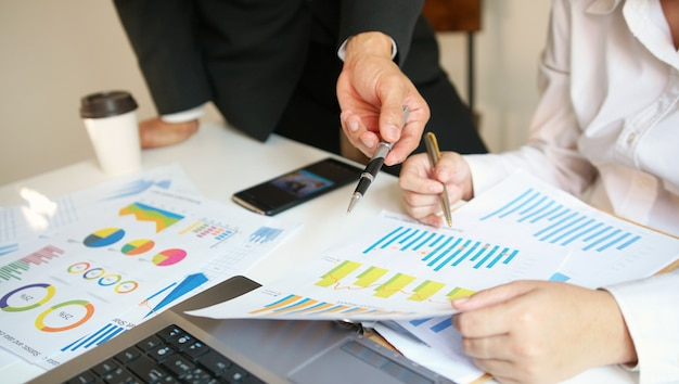 Ludzie biznesu pracuje wpólnie dyskutujący pieniężnego diagram, praca zespołowa
