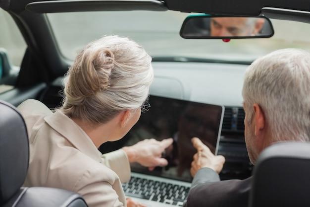 Ludzie biznesu pracuje wpólnie na laptopie w z klasą kabriolecie