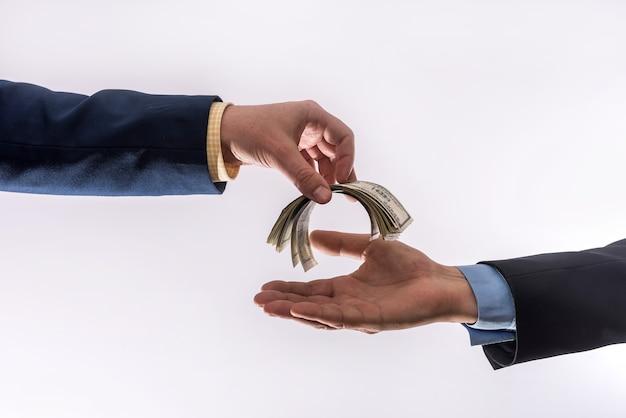 Ludzie biznesu przekazują nam pieniądze na białym tle na szarej ścianie. koncepcja finansów