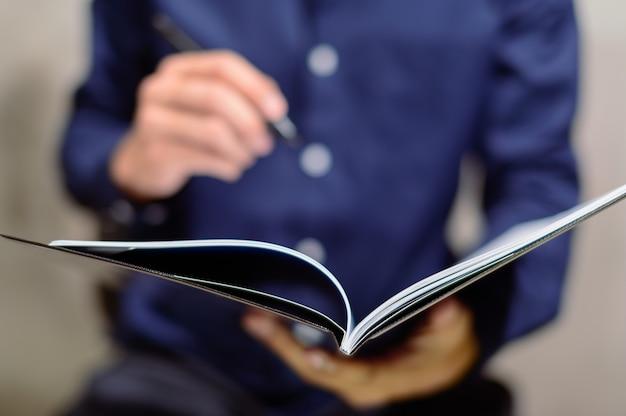 Ludzie biznesu robią notatki w papierowych książkach