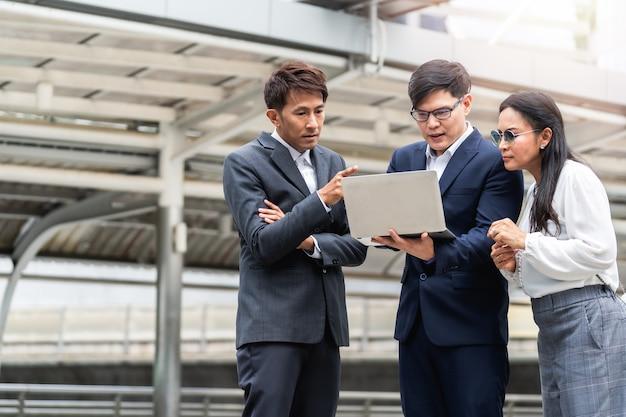 Ludzie biznesu rozmawiają o laptopie i pracują razem na świeżym powietrzu