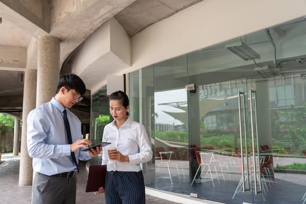 Ludzie biznesu rozmawiają podczas przerwy, omawiając nowy projekt biznesowy poza biurem w mieście.