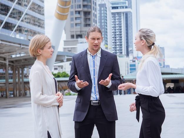 Ludzie biznesu rozmawiają poza biurem, spotkanie na zewnątrz