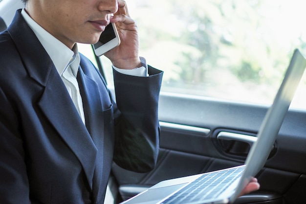 Ludzie biznesu rozmawiają przez telefon i szukają informacji na laptopie podczas podróży, aby negocjować poza firmą.