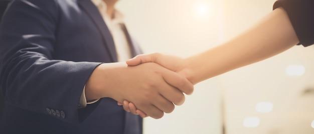 Ludzie biznesu, ściskając ręce, między spotkaniami w sali seminaryjnej