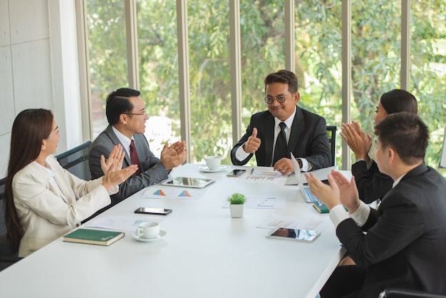 Ludzie biznesu spotyka razem przy biurowym stołem z cieszyć.