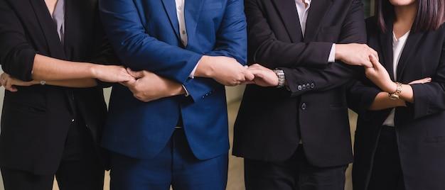 Ludzie biznesu spotykają ręki wpólnie w linii. młodzi ludzie biznesu trzymają się za ręce.