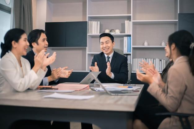 Ludzie biznesu spotykają się i omawiają dokumenty i pomysły na spotkaniu przy stole.