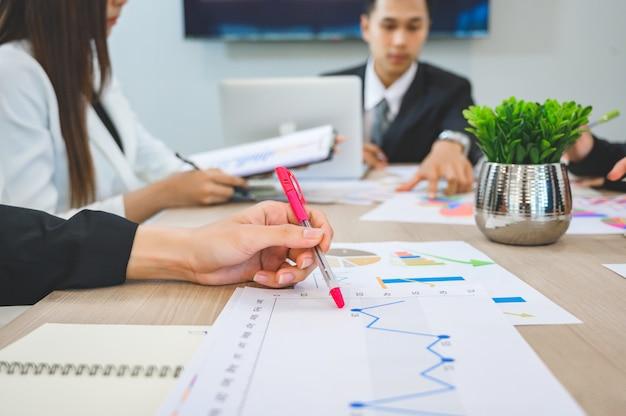 Ludzie biznesu spotykają się i przedstawiają wykresy wzrostu biznesu na biurku