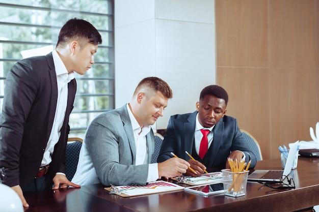 Ludzie biznesu spotykają się wokół stołu sali konferencyjnej, omawiając strategię