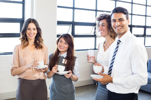 Ludzie biznesu stały i razem i uśmiechając się w biurze