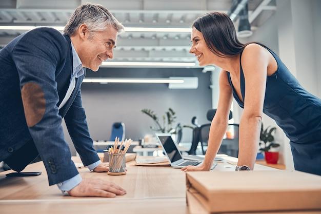 Ludzie biznesu stoją twarzą do siebie w sali konferencyjnej i śmieją się podczas pracy
