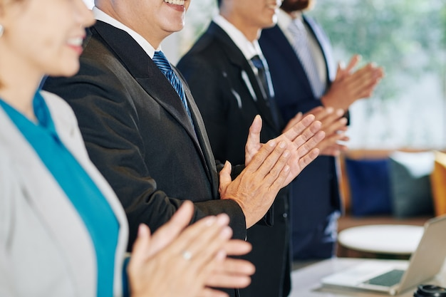 Ludzie biznesu stojący przy klaskaniu do współpracownika po jego inspirującej przemowie