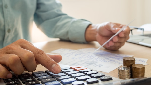 Ludzie biznesu stresują się problemami finansowymi, użyj kalkulatora, aby obliczyć koszt pokwitowań umieszczonych na stole. pojęcie długu