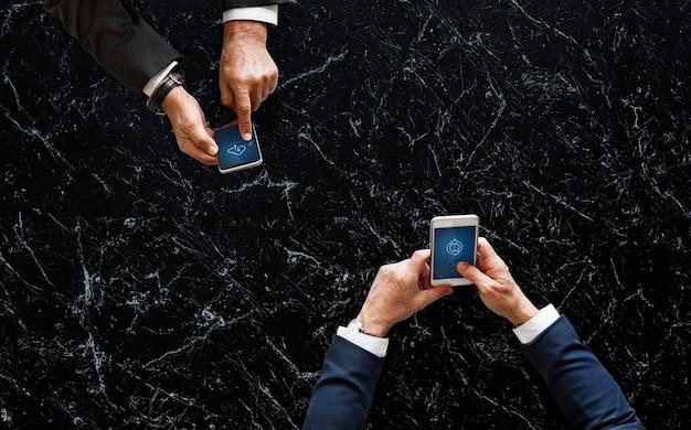 Ludzie biznesu synchronizowanie danych przez telefon komórkowy