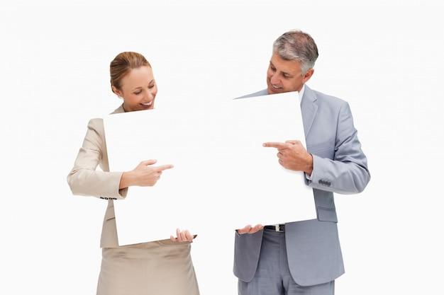 Ludzie biznesu trzyma plakat i wskazuje