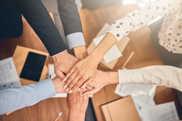 Ludzie biznesu trzymający się za ręce podczas spotkania