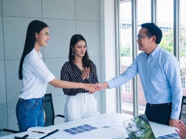 Ludzie biznesu uścisnąć dłoń w biurze