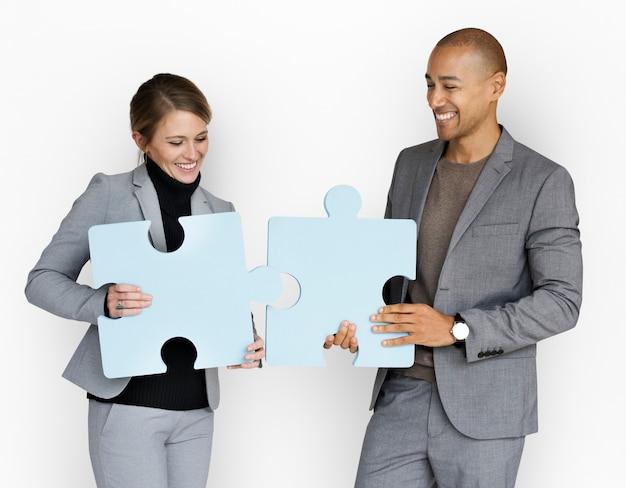 Ludzie biznesu uśmiecha się szczęście trzyma wyrzynarki łamigłówki pojęcie
