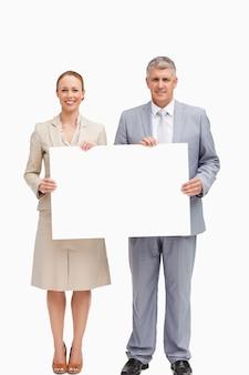 Ludzie biznesu uśmiecha się trzymając plakat