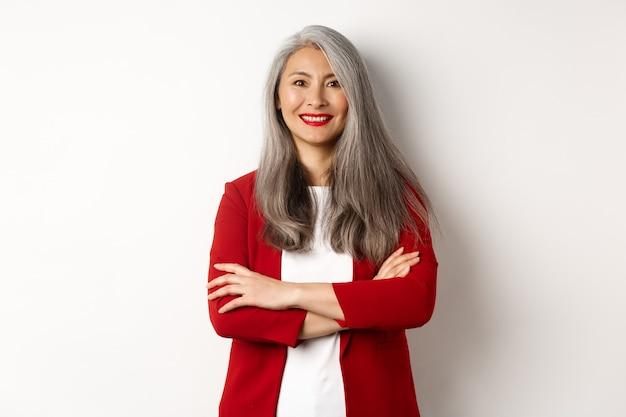 Ludzie biznesu. uśmiechnięta azjatycka starsza kobieta w czerwonej marynarce, skrzyżowane ramiona na klatce piersiowej i patrząc profesjonalnie, stojąc na białym tle.