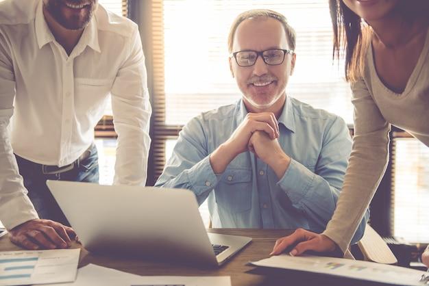 Ludzie biznesu używają laptopa, omawiając sprawy.