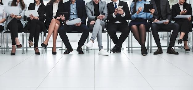 Ludzie biznesu używają swoich gadżetów przed rozpoczęciem spotkania biznesowego