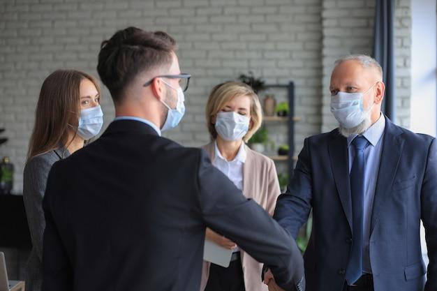 Ludzie biznesu w maskach medycznych, ściskając ręce, kończąc spotkanie.