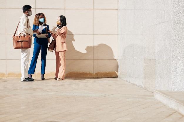 Ludzie biznesu w maskach ochronnych stoją na zewnątrz i odbywają szybką odprawę przed spotkaniem z partnerami biznesowymi
