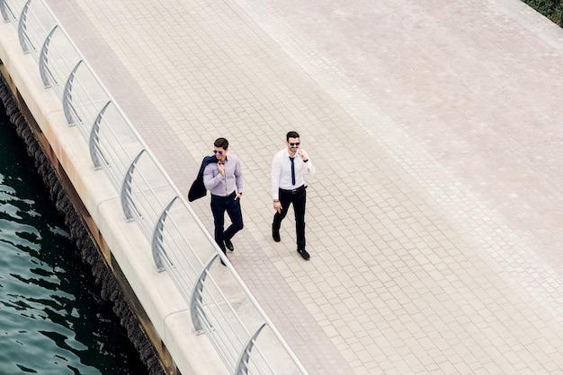Ludzie biznesu w ruchu. dwóch młodych architektów odnoszących sukcesy w dubai marine spaceruje i przygląda się nowym lokalizacjom biznesowym. widok z góry.