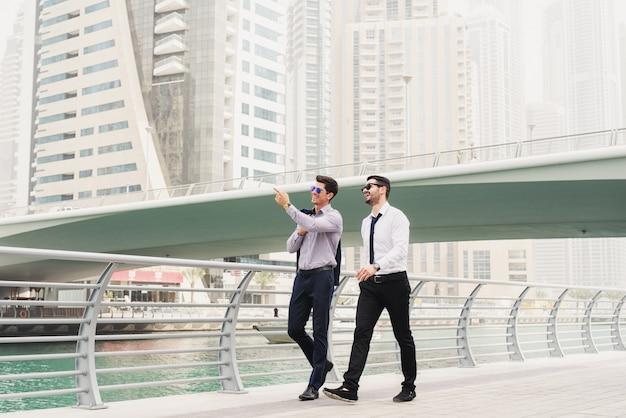 Ludzie biznesu w ruchu. dwóch młodych architektów odnoszących sukcesy w dubai marine spaceruje i przygląda się nowym lokalizacjom biznesowym.