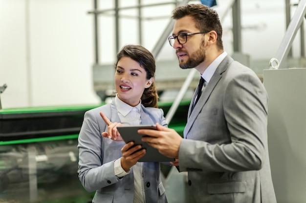 Ludzie biznesu w środowisku pracy wewnątrz fabryki. mężczyzna i kobieta w eleganckim garniturze przyglądają się pracy w produkcji. trzymają tablet, podczas gdy pani wyjaśnia proces mężczyźnie