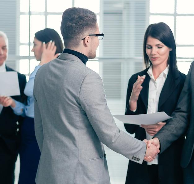 Ludzie biznesu witają się uściskiem dłoni w holu biura. pomysł na biznes