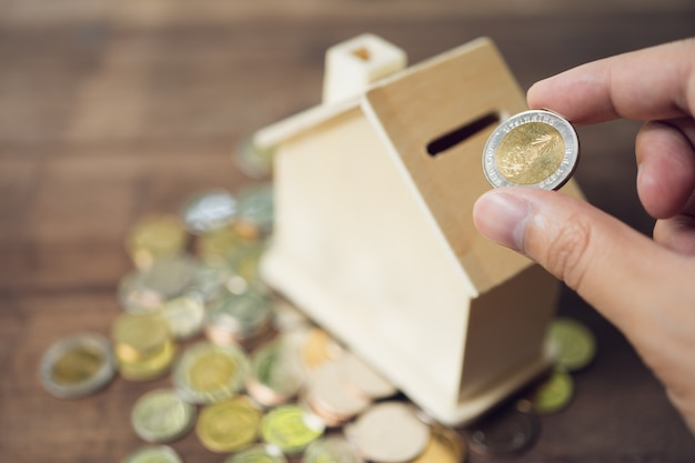 Ludzie biznesu włóż monetę do skarbonki w stylu house aby zaoszczędzić pieniądze, zaoszczędź pieniądze