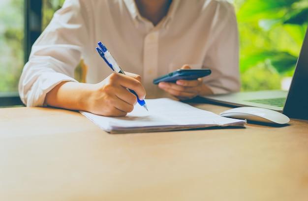 Ludzie biznesu wręczają mienie telefon komórkowego i wypełnia papierkową robotę z laptopem na stole.