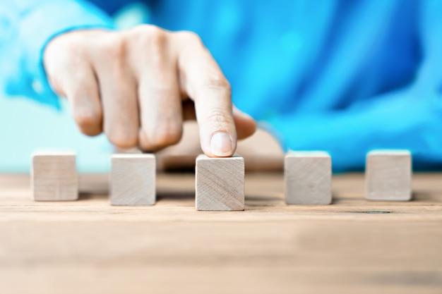 Ludzie biznesu wskazują drewniany blok z kopii przestrzenią.