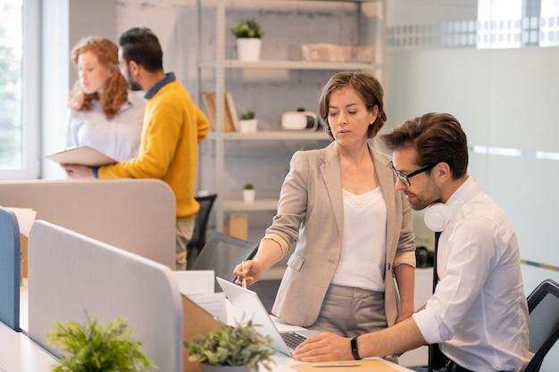 Ludzie biznesu wspólnie omawiający prezentację: doświadczona kierownik projektu wskazująca na ekran laptopa i wyjaśniająca informacje młodemu mężczyźnie