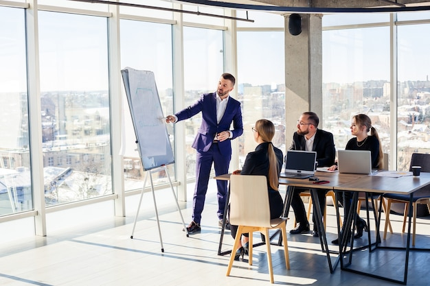 Ludzie biznesu współpracujący w nowoczesnym biurze z widokiem na panoramę miasta. reżyser opowiada pracownikom o nowych technologiach. koncepcja pracy biurowej