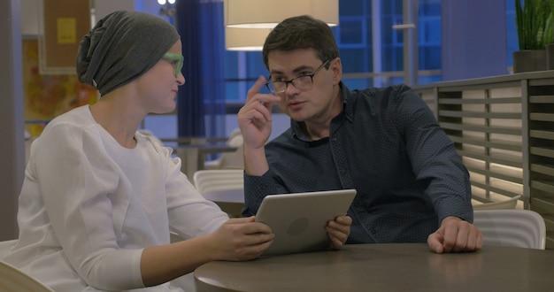 Ludzie biznesu z komputerem typu tablet omawiają sprawę