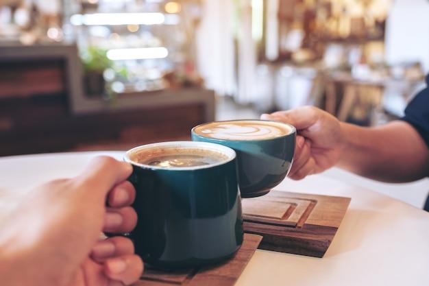 Ludzie brzęczą kubkami kawy w kawiarni