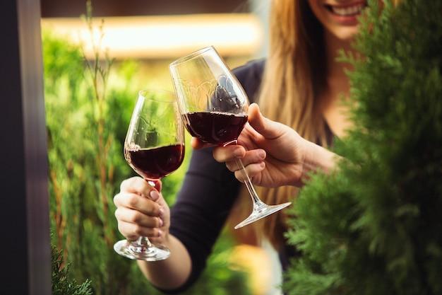 Ludzie brzęk kieliszków z winem na letnim tarasie kawiarni lub restauracji. wesoły wesoły przyjaciele świętują letni lub jesienny fest. bliska strzał ludzkich rąk, styl życia.