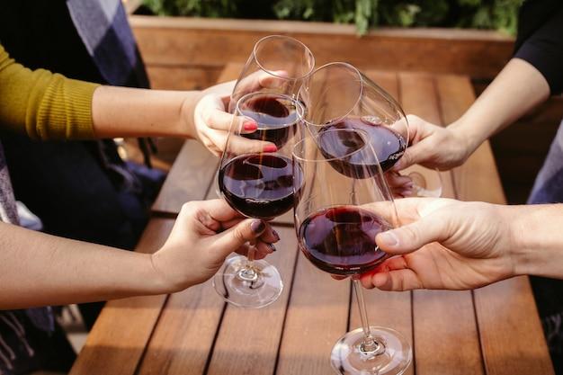 Ludzie brzęk kieliszków z winem na letnim tarasie kawiarni lub restauracji. wesołych wesołych przyjaciół świętują letni lub jesienny fest. bliska strzał ludzkich rąk, styl życia.