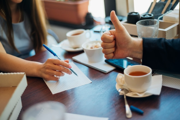 Ludzie burzy mózgów pije herbatę w kawiarni