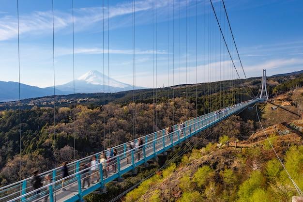 Ludzie chodzą na moście mishima skywalk z mount fuji widzianym w odległym, jasnym słonecznym dniu